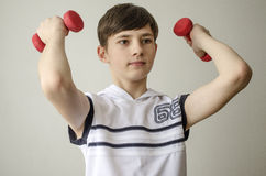 Teenager boy in a white shirt without sleeves is doing exercises with dumbbells Royalty Free Stock Photo