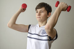 Teenager boy in a white shirt without sleeves is doing exercises with dumbbells Stock Photo