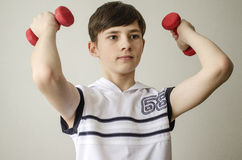Teenager boy in a white shirt without sleeves is doing exercises with dumbbells Royalty Free Stock Images
