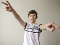 Teenager boy in a white shirt without sleeves with hands outstretched in a gesture of victory Stock Images