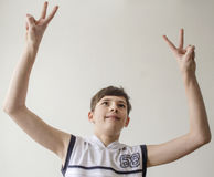 Teenager boy in a white shirt without sleeves with hands outstretched in a gesture of victory. On a light background Stock Images