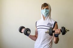 Teenager boy in a white T-shirt with a hood and medical mask is training with two dumbbells.