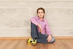 Teenager boy worried sitting on the floor Stock Photo