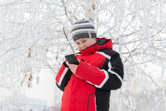 Teenager boy writes sms in winter park Stock Photos