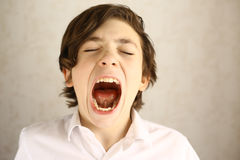 Teenager boy yawning open mouth. Close up portrait Stock Photos
