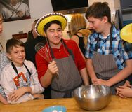 Teenager boys cooking. Moscow, Russia, December 16, 2017: Unidentified teenager boys cooking profiterols  on culinary master class lesson  party signifying final Stock Photos