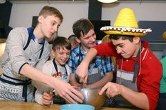 Teenager boys cooking. Moscow, Russia, December 16, 2017: Unidentified teenager boys cooking profiterols  on culinary master class lesson  party signifying final Royalty Free Stock Photo