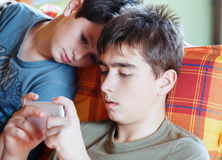 Teenager boys playing on smartphone, outdoor Stock Photo