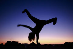Teenager breakdancing at sunset. Silhouette of an athletic teenager breakdancing at sunset silhouetted against the colourful sky balance upside down on one hand Stock Photos