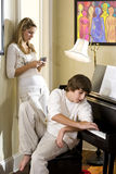 Teenager brother and sister at home by piano Stock Images