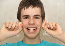 Teenager with dental floss Stock Photo