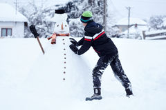 Teenager building a snowman. Teenage boy building a snowman in the countryside Stock Photography