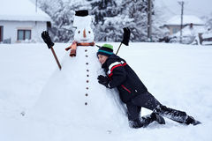 Teenager building a snowman. Teenage boy building a snowman in the countryside Stock Photos