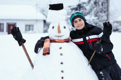 Teenager building a snowman. Teenage boy building a snowman in the countryside Royalty Free Stock Image