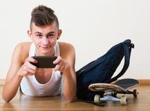 Teenager burying in mobile phone Royalty Free Stock Photos