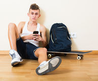 Teenager burying in mobile phone Royalty Free Stock Images