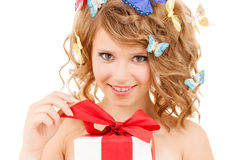 Teenager with butterflies in hair opening present. Health, holidays and beauty concept - happy teenage girl with butterflies in hair opening gift box Royalty Free Stock Photo