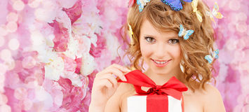 Teenager with butterflies in hair opening present. Health, holidays and beauty concept - happy teenage girl with butterflies in hair opening gift box Royalty Free Stock Photography
