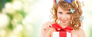 Teenager with butterflies in hair opening present. Health, holidays and beauty concept - happy teenage girl with butterflies in hair opening gift box Stock Photos