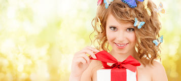 Teenager with butterflies in hair opening present. Health, holidays and beauty concept - happy teenage girl with butterflies in hair opening gift box Royalty Free Stock Photos