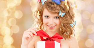 Teenager with butterflies in hair opening present. Health, holidays and beauty concept - happy teenage girl with butterflies in hair opening gift box Stock Image