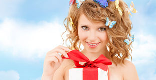 Teenager with butterflies in hair opening present. Health, holidays and beauty concept - happy teenage girl with butterflies in hair opening gift box Royalty Free Stock Image