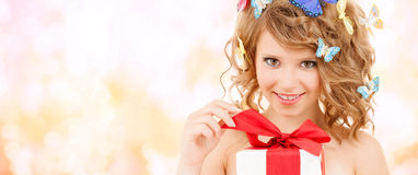 Teenager with butterflies in hair opening present Stock Photos