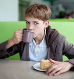 Teenager in cafe eating fast food Royalty Free Stock Photos