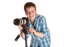 Teenager with camera. Young photographer teenager taking photos with a camera on a tripod Stock Photography