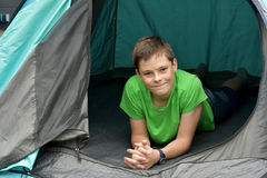 Teenager at camping vacations. Teenage boy at camping relaxing in a tent Royalty Free Stock Image