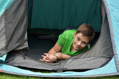 Teenager at camping vacations. Teenage boy at camping relaxing in a tent Stock Images