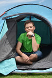Teenager at camping vacations. Teenage boy at camping relaxing in a tent Royalty Free Stock Images