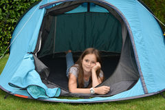 Teenager at camping vacations. Teenage girl at camping relaxing in a tent Royalty Free Stock Images