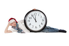 Teenager in cap of Santa Claus and large clock Stock Photo