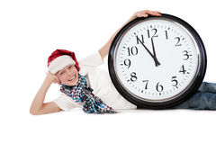 Teenager in cap of Santa Claus and large clock Stock Images