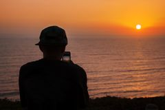 Sunset view of the Pacific ocean in Lima, Peru. Teenager in the cap shooting sunset with his smartphone royalty free stock images