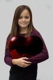 Teenager carries a big red heart Stock Photography