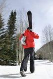 Teenager carrying ski gear. Royalty Free Stock Photos