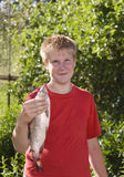 Teenager with caught fish Royalty Free Stock Photos