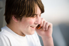 Teenager on cellphone laughing. Teenager male on cellphone laughing. A natural portrait royalty free stock photography