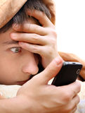 Teenager with Cellphone. Surprised Teenager with Cellphone under Blanket on the Bed Royalty Free Stock Photography
