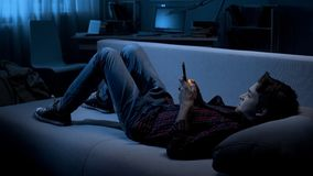 Teenager chatting with friends on smartphone lying on couch, social network. Stock photo stock photo