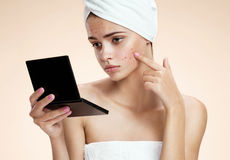 Teenager checking her face for pimple looking in the mirror. Woman with skin blemish looking at mirror isolated, beige background Stock Images