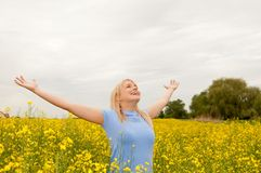 Teenager cheering in the rape field Stock Images