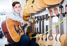 Teenager choosing acoustic guitars. Smiling male teenager examining various acoustic guitars in guitar store Royalty Free Stock Photo