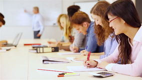 Teenager in classroom learning from teacher. At the whiteboard (Full HD stock video footage