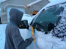 Teenager cleaning snow off a vehicle Stock Photo
