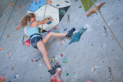 Teenager climbing a rock wall Royalty Free Stock Photos