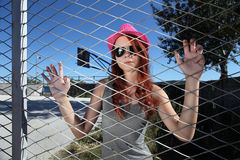 Teenager clings to the metal mesh of the playground Royalty Free Stock Photography