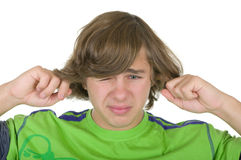 Teenager closes ears fingers. On a white background Stock Image